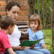 Mother with children sit on bench and read book — Stock Photo