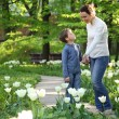 Stock Photo: Mother shows to son blossoming white tulips in garden