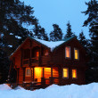 Wooden house in winter wood in twilight — Stock Photo