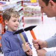 Stock Photo: Elderly mwith boy in shop with hammers in hands
