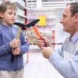 Stock Photo: Elderly man with boy in shop with hammers in hands