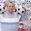Elderly man in shop with footballs in hands - Stok fotoraf