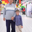 Elderly man with boy in shop — Stock Photo