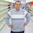 Elderly man stands between empty shelves in shop — Stock Photo #7425776