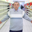 Elderly man stands between empty shelves in shop with dissolved — Stock Photo