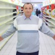 Elderly man stands between empty shelves in shop with dissolved — Stock Photo #7425781