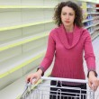 Young woman with  cart in shop with empty shelves — Stock Photo