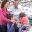Elderly man and young woman with children in shop with empty sh — Stock Photo