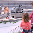 Young woman with child and bored seller in shop with empty shelv — Stock Photo #7425824