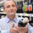 Happy elderly man in shop looks on  wine bottle in hands — Stockfoto
