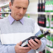 Elderly man in shop looks on wine bottle in hands — Stock Photo #7425855