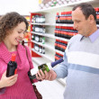 Happy girl and  elderly man in shop with wine bottles in hands — Photo