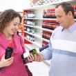 Happy girl and  elderly man in shop with wine bottles in hands — Stok fotoğraf