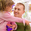 Smiling young man with little girl buy yogurt in supermarket — Stock Photo