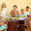 Big happy family with children eats fruit in cosy room — Stock Photo