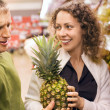 Smiling young man and woman buy pineapple in supermarket — Stock Photo