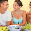 Smiling man and two young women eat fruit in cosy room — Stock Photo