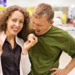 usmívající se mladý muž a žena koupit broskve v supermarketu — Stock fotografie