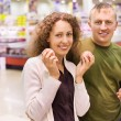 Smiling young man and woman buy peaches in supermarket — Stock Photo
