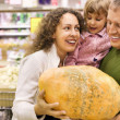 Family with little girl buy pumpkin in supermarket — Foto de Stock