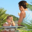 Little girl and young woman eat ice-cream near palm trees on res — Stock Photo #7426565