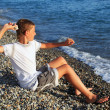 Sitting boy throws stone in sea - Stock Photo