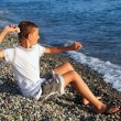 Sitting boy throws stone in sea - Photo