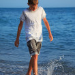 Teenager boy going on seacoast - Stock Photo