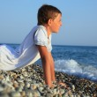 Stock Photo: Teenager boy lying on stones on seacoast
