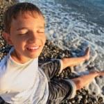 Sitting teenager boy on stone seacoast, closed eyes, wets feet i — Stock Photo #7426604