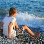 Sitting teenager boy on stone seacoast, wets feet in water, sitt — Stock Photo