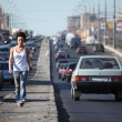 Girl goes on highway middle in city — Stock Photo #7426643