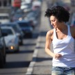 Girl runs on highway middle in city, view on belt — Stock Photo #7426660