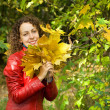 Young woman with maple leaves in hands near tree in wood in autu — Stock Photo #7426665