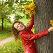 young woman with maple leaves in hands near tree in wood in autu — Stock Photo #7426678