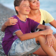 Young woman embraces smiling boy on beach in evening, Looking af — Stock Photo