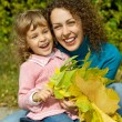 Young woman and little girl laugh with leaves in hands in garden — Stock Photo #7426737