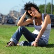 Girl sits on lawn at road in city — Stock Photo