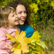 Young woman and little girl laugh with leaves in hands in garden — Stock Photo #7426742