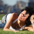 Girl lies on lawn at road in city — Stock Photo #7426754