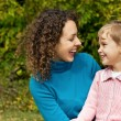 Young woman and little girl laugh in garden — Stock Photo #7426759
