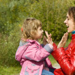 Young woman and little girl playing in okie dokey in garden - Stock Photo