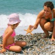 Young woman gives starfish to little girl on stony beach — Stock Photo #7426787