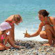 Young woman gives starfish to two little girls on stony beach — Stock Photo #7426790