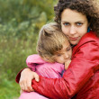 Young woman protects little girl from wind in garden - Стоковая фотография