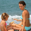 Stock Photo: Young woman with little girl played starfish on stony beach