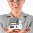 Business woman in glasses holds model of house — Stock Photo #7426913