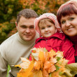 Happy family of three persons in the autumn park — Stock Photo