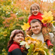 Royalty-Free Stock Photo: Married couple and little girl collect maple leafs In park in au