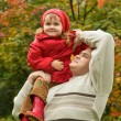Little girl sits on shoulder at man In park in autumn — Stock Photo